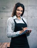 Happy beautiful female waiter in apron Stock Photography