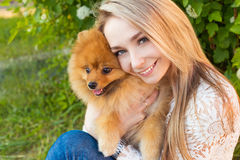 Happy beautiful gentle girl hugging her pet dog red Spitz Stock Photos