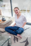 Happy beautiful girl with bare feet enjoying sitting on floor. Happy beautiful young girl with bare feet enjoying sitting on her living room floor for wellbeing stock photos