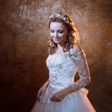 Happy Beautiful girl bride in luxurious wedding dress, portrait in Golden tones, effects of glare. Beautiful girl bride in a luxurious wedding dress, portrait in Stock Image