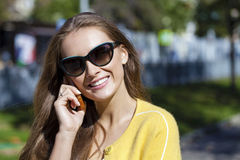 Happy beautiful girl calling by phone Stock Image