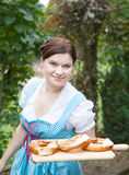 Happy beautiful woman in dirndl dress holding pretzels Stock Photography