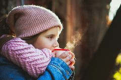 Girl drinking hot tea from the thermos stock photo