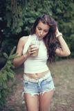 Happy beautiful girl drinking ice coffee in the park Stock Images