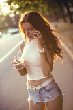 Happy beautiful girl drinking ice coffee and talking on the phone Royalty Free Stock Photo