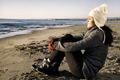 Happy beautiful girl enjoying beach in winter with hat Royalty Free Stock Image