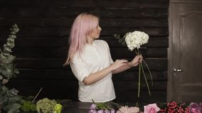 Happy, beautiful girl florist in a white shirt enthusiastically chooses flowers for a composition from a wide assortment. Of flowers. Slow motion stock footage