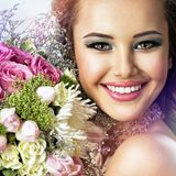 Happy beautiful girl with flowers in hands stock photography