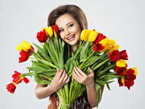 Happy beautiful girl with flowers in hands. Portrait of beautiful happy woman with flowers in hands. Young attractive young girl holds the bouquet of red and Stock Photography