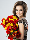 Happy beautiful girl with flowers in hands. Portrait of beautiful happy woman with flowers in hands. Young attractive young girl holds the bouquet of red and Stock Photo