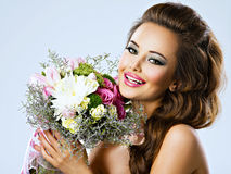 Happy beautiful girl with flowers in hands. Portrait of beautiful happy girl with flowers in hands. Young attractive woman holds the bouquet of spring flowers Royalty Free Stock Images