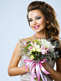 Happy beautiful girl with flowers in hands. Portrait of beautiful happy girl with flowers in hands. Young attractive woman holds the bouquet of spring flowers Stock Images