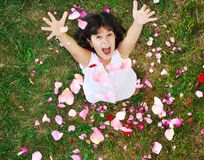 Happy beautiful girl on ground with rose's petals Stock Images