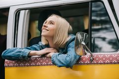 Happy beautiful girl. Happy beautiful blonde girl sitting in retro styled minivan Royalty Free Stock Image