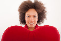 Happy beautiful girl with heart shaped red pillow royalty free stock photos