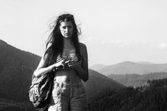 Happy beautiful girl hipster traveling on top hill on background of amazing sky and mountains in summer, black and white. Happy beautiful girl hipster traveling royalty free stock photo