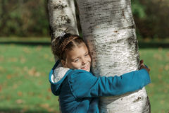 happy beautiful girl hugging a birch tree in park on sunny autumn warm day Stock Photo