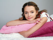 The happy beautiful girl lies on pink pillows royalty free stock images