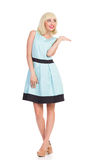 Happy beautiful girl in light blue color dress presenting product Stock Photo