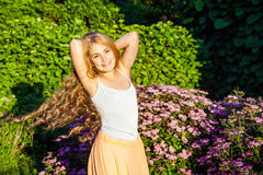 Happy beautiful girl with long light brown hair is posing in the park. Happy beautiful girl with long light brown hair is posing in the park royalty free stock image