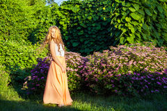 Happy beautiful girl with long light brown hair is posing in the park. Happy beautiful girl with long light brown hair is posing in the park royalty free stock photo