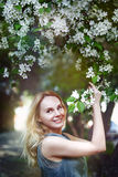 Happy beautiful girl in the park in flowers. Spring, wind, freedom. Small amount of grain added for best final impression Royalty Free Stock Photography