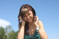 Happy beautiful girl with phones on skies Stock Photo