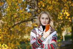 Happy beautiful girl photographed on a cell phone in autumn park Stock Photos