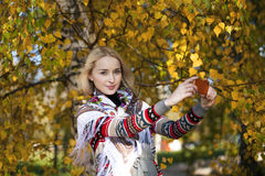 Happy beautiful girl photographed on a cell phone in autumn park Stock Photography