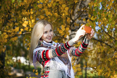 Happy beautiful girl photographed on a cell phone in autumn park Royalty Free Stock Photo