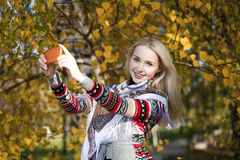 Happy beautiful girl photographed on a cell phone in autumn park Royalty Free Stock Images