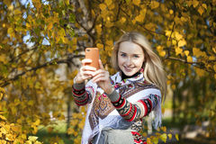 Happy beautiful girl photographed on a cell phone in autumn park Royalty Free Stock Image