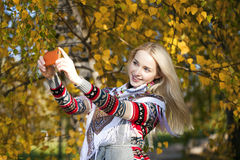 Happy beautiful girl photographed on a cell phone in autumn park Stock Photo