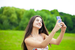 Happy beautiful girl photographed on a cell phone in a summer pa Stock Images