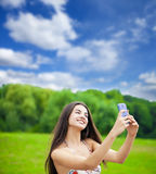 Happy beautiful girl photographed on a cell phone in a summer pa Royalty Free Stock Images