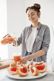 Happy beautiful girl pouring grapefruit detox smoothie in glass smiling over white wall. Healthy diet nutrition. Stock Images