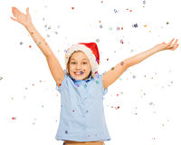 Happy beautiful girl in Santa cap throw confetti. Happy beautiful girl in Santa cap throw up confetti with lifted hands and cute smile royalty free stock photography