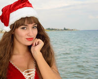 Happy and beautiful girl Santa Claus on the beach. Beautiful young brunette woman dressed as Santa Claus stock photos