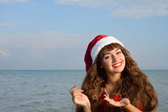 Happy and beautiful girl Santa Claus on the beach. Royalty Free Stock Images