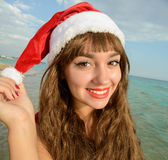 Happy and beautiful girl Santa Claus on the beach. Stock Image