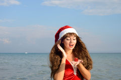 Happy and beautiful girl Santa Claus on the beach. Stock Photography