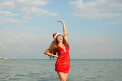 Happy and beautiful girl Santa Claus on the beach. Beautiful young brunette woman dressed as Santa Claus royalty free stock photo