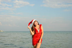 Happy and beautiful girl Santa Claus on the beach. Beautiful young brunette woman dressed as Santa Claus stock photo