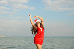 Happy and beautiful girl Santa Claus on the beach. Beautiful young brunette woman dressed as Santa Claus royalty free stock photography