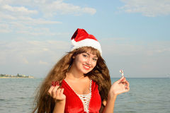 Happy and beautiful girl Santa Claus on the beach. Beautiful young brunette woman dressed as Santa Claus royalty free stock photos