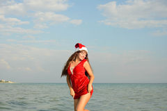 Happy and beautiful girl Santa Claus on the beach. Beautiful young brunette woman dressed as Santa Claus stock photography