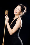 Happy beautiful girl singer laughing behind retro microphone royalty free stock photos