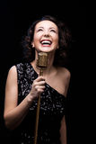 Happy beautiful girl singer laughing holding retro microphone Stock Images