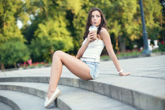 Happy beautiful girl sitting on stairs in park and drinking ice coffee Royalty Free Stock Images