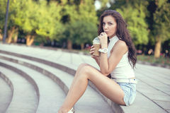 Happy beautiful girl sitting on stairs in park and drinking ice coffee.  Stock Photography